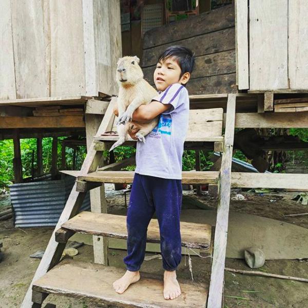 A boy holds his pet capybara
